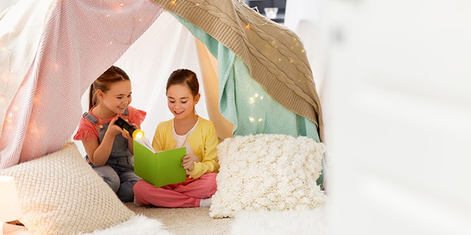 Two little girls reading in cozy tent with pillows.