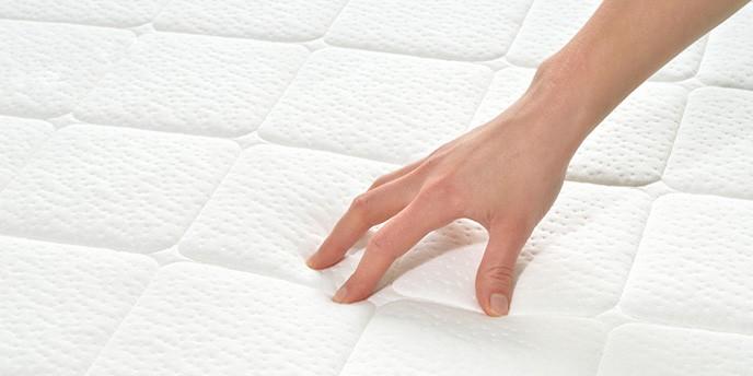 Person's hand testing mattress firmness.