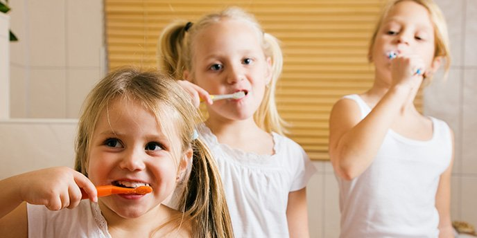 Three Young Girls Brushing Their Teeth