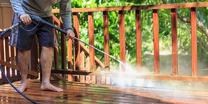 Man Pressure Washing Wood Deck