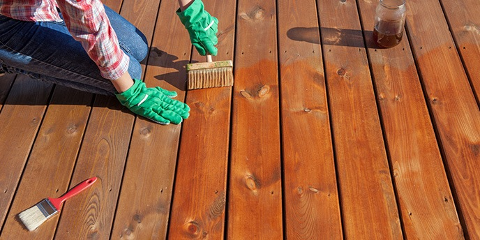 Woman Wearing Gloves to Stain Wood Deck Boards