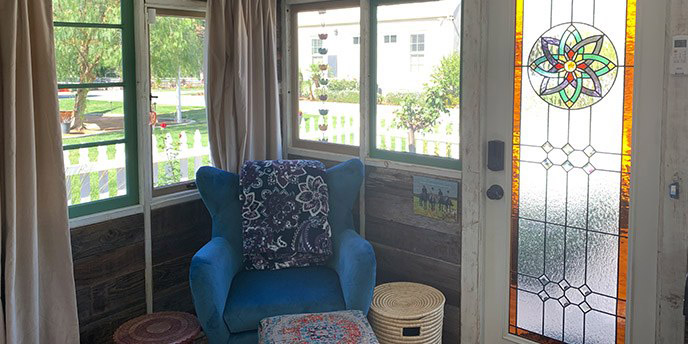 She Shed Interior with Blue Accent Chair and Stained Glass Door