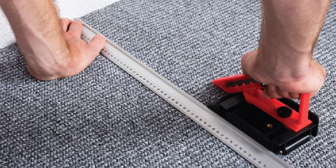 Homeowner Using Carpet Stretcher During Installation