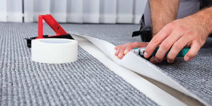 Homeowner With Tools Installing Strips of Carpet