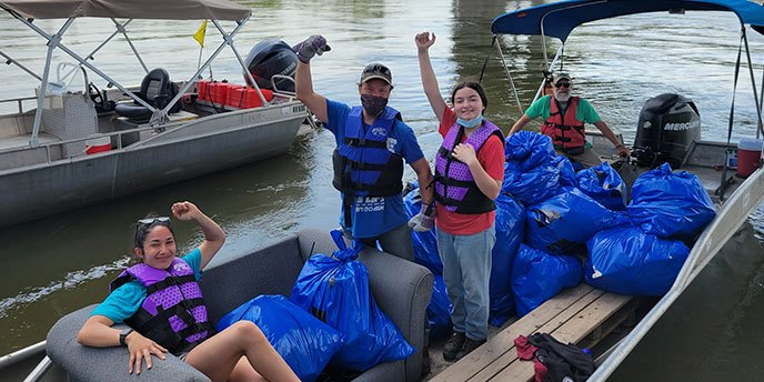 Volunteers Carry Trash Onto a Boat