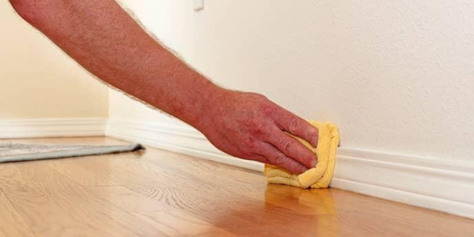 Hand Wiping Down a Baseboard