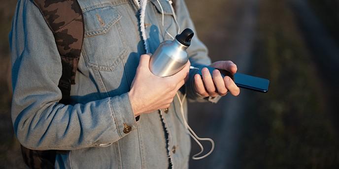 Man Carrying Metal Water Bottle Outside