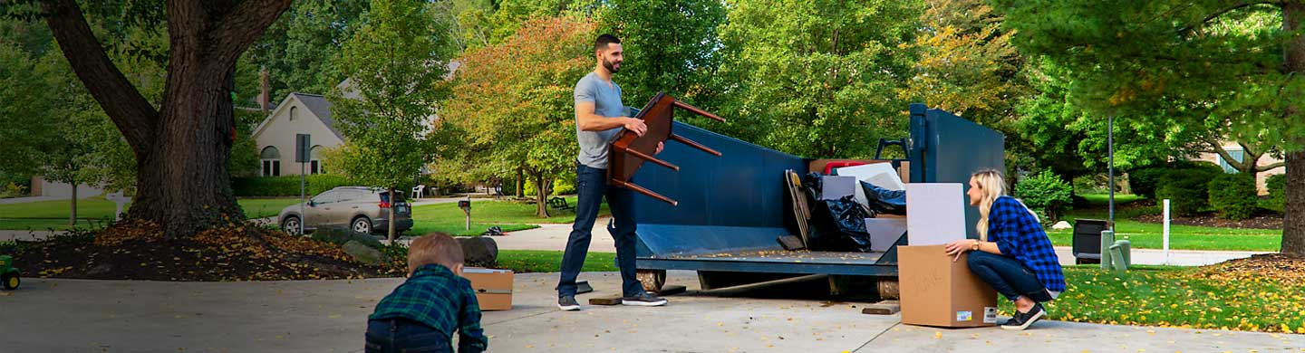 Family loading old furniture and boxes into a blue roll off dumpster.