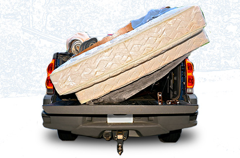 Pickup Truck Bed Filled With Mattress and Other Junk