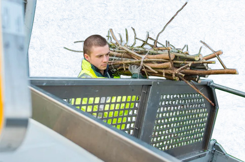 Worker Loading Stack of Branches Into Truck